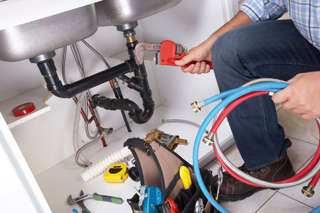 Picture of a plumber repairing a kitchen sink.